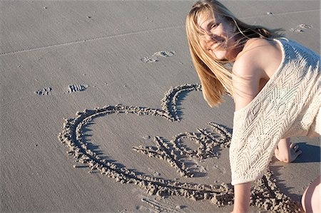 symbol - Smiling woman writing love message in sand, Breezy Point, Queens, New York, USA Stock Photo - Premium Royalty-Free, Code: 614-07234840