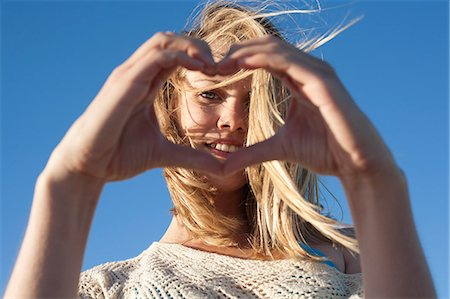 Portrait of young woman making heart sign, Breezy Point, Queens, New York, USA Stock Photo - Premium Royalty-Free, Code: 614-07234841