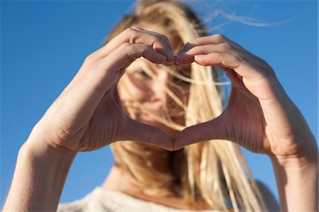 symbol - Young woman making heart sign with hands, Breezy Point, Queens, New York, USA Stock Photo - Premium Royalty-Free, Code: 614-07234842