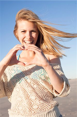 Smiling woman making heart sign with hands, Breezy Point, Queens, New York, USA Stock Photo - Premium Royalty-Free, Code: 614-07234843