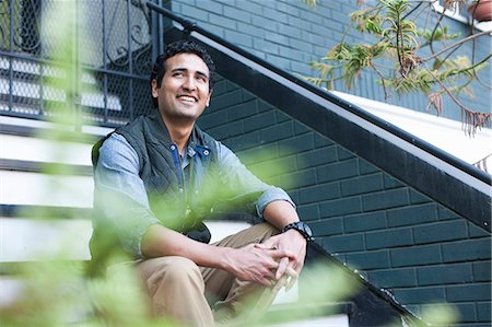 Portrait of young man sitting on steps Stock Photo - Premium Royalty-Free, Code: 614-07234877