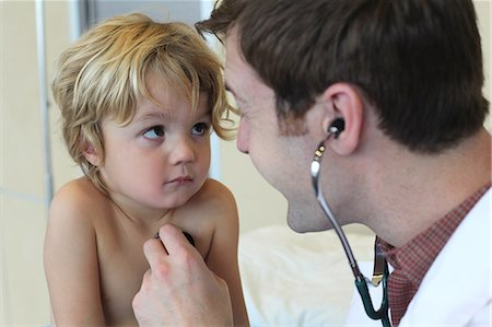 Young male doctor listening to boys chest in clinic Stock Photo - Premium Royalty-Free, Code: 614-07234913