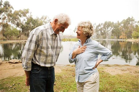 senior women - Husband and wife sharing joke by the lake Stock Photo - Premium Royalty-Free, Code: 614-07234966