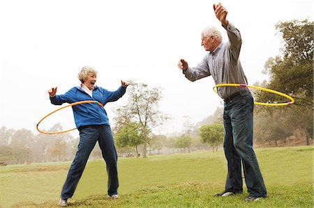 Husband and wife playing hula hoop in the park Stock Photo - Premium Royalty-Free, Code: 614-07234961