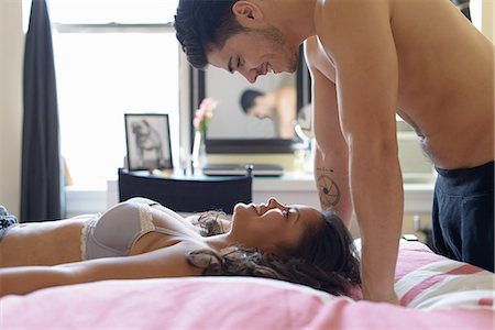 Young couple in bed, woman lying on back with man above Stock Photo - Premium Royalty-Free, Code: 614-07234995