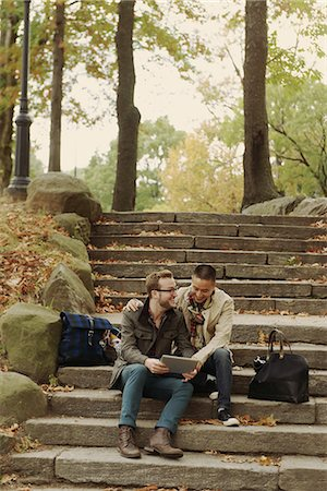 Gay couple using digital tablet on steps Stock Photo - Premium Royalty-Free, Code: 614-07239946