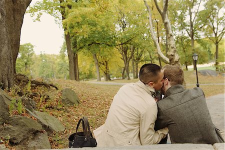 Man kissing partner on cheek in park Stock Photo - Premium Royalty-Free, Code: 614-07239948