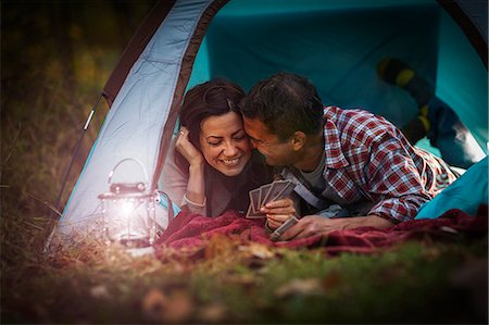 Mature couple lying together in tent, playing card game Stock Photo - Premium Royalty-Free, Code: 614-07239969