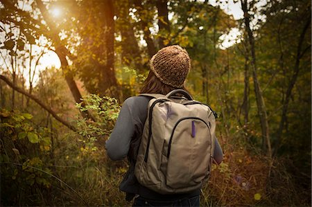 Rear view of woman walking through forest, carrying rucksack Stock Photo - Premium Royalty-Free, Code: 614-07239976