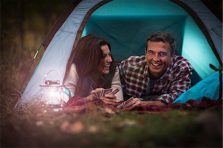 Mature couple lying together in tent, playing card game Stock Photo - Premium Royalty-Free, Code: 614-07239970