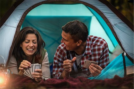 Mature couple lying together in tent, playing card game Stock Photo - Premium Royalty-Free, Code: 614-07239971