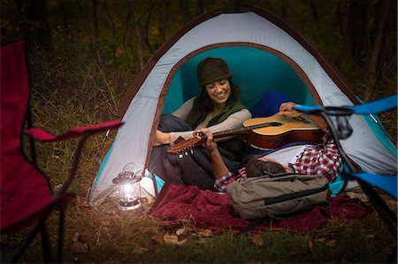 Mature couple sitting in tent, playing guitar Stock Photo - Premium Royalty-Free, Code: 614-07239983