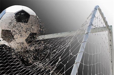 Studio shot of football powering through goal netting Stock Photo - Premium Royalty-Free, Code: 614-07239995