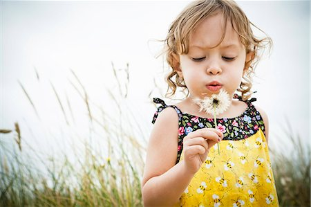 Portrait of female toddler with dandelion clock Stock Photo - Premium Royalty-Free, Code: 614-07240004