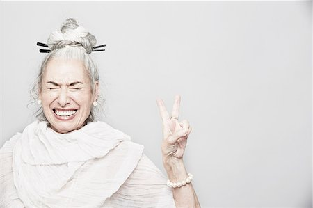 Studio portrait of sophisticated senior woman making victory sign Stock Photo - Premium Royalty-Free, Code: 614-07240022