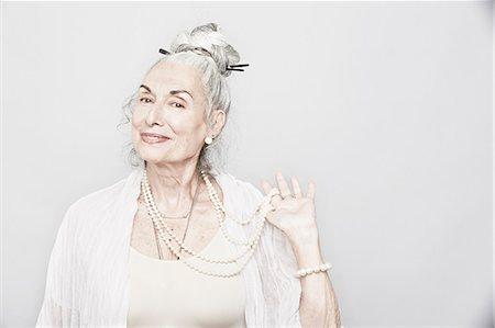 style - Studio portrait of sophisticated senior woman holding beads Stock Photo - Premium Royalty-Free, Code: 614-07240023