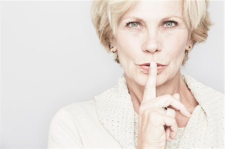 Cropped studio portrait of senior woman with finger on lips Stock Photo - Premium Royalty-Free, Code: 614-07240031