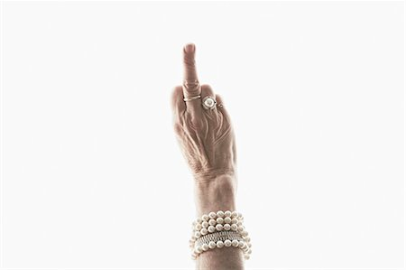 Studio shot of mature woman's hand making obscene gesture Stock Photo - Premium Royalty-Free, Code: 614-07240051
