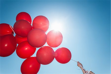 Hands holding bunch of red balloons against blue sky Stock Photo - Premium Royalty-Free, Code: 614-07240062