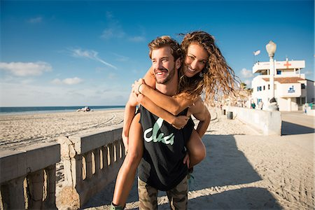 Young man giving girlfriend a piggy back at San Diego beach Stock Photo - Premium Royalty-Free, Code: 614-07240086