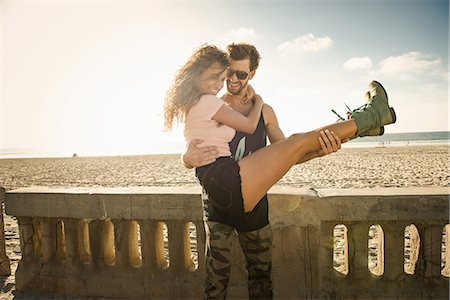 Young man holding girlfriend in arms at San Diego beach Stock Photo - Premium Royalty-Free, Code: 614-07240087