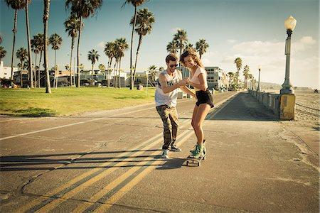 Young woman on skateboard at San Diego beach, boyfriend helping Stock Photo - Premium Royalty-Free, Code: 614-07240081