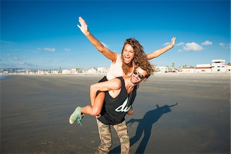 Young woman on boyfriend's back with arms raised Stock Photo - Premium Royalty-Free, Code: 614-07240083