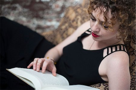 style - Portrait of young woman reclining and reading book Stock Photo - Premium Royalty-Free, Code: 614-07240103