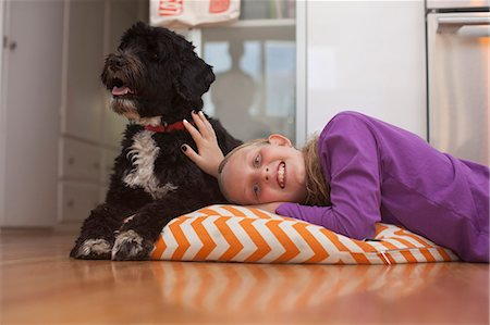 preteen girl - Portrait of girl lying on cushion with pet dog Stock Photo - Premium Royalty-Free, Code: 614-07240147