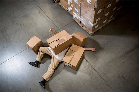 Man lying on floor covered by cardboard boxes in warehouse Stock Photo - Premium Royalty-Free, Code: 614-07240170