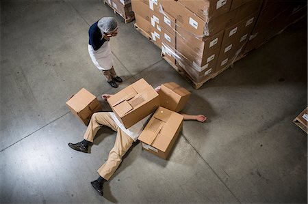 funny looking people - Woman looking at man lying on floor covered by cardboard boxes in warehouse Stock Photo - Premium Royalty-Free, Code: 614-07240171