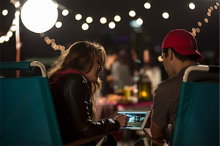 Young couple looking at digital tablet at rooftop barbecue Stock Photo - Premium Royalty-Free, Code: 614-07240205
