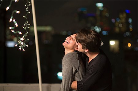 Young couple embracing at rooftop party Stock Photo - Premium Royalty-Free, Code: 614-07240206
