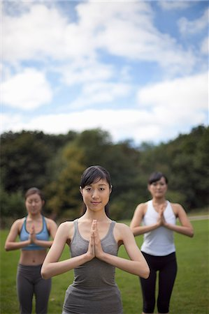 Three young women in park practicing yoga Stock Photo - Premium Royalty-Free, Code: 614-07444013