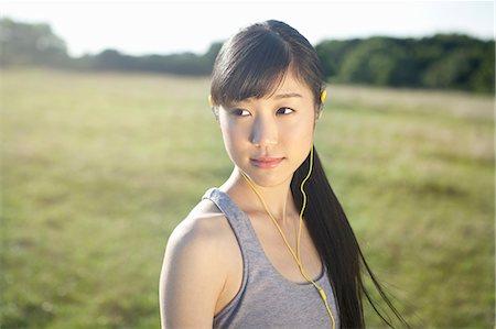 portrait looking away - Portrait of young female runner wearing earphones Stock Photo - Premium Royalty-Free, Code: 614-07444021