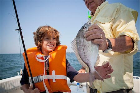 Boy and grandfather with caught fish on boat,  Falmouth, Massachusetts, USA Stock Photo - Premium Royalty-Free, Code: 614-07444057