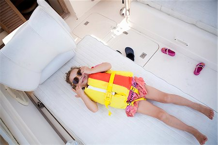 Female toddler hiding in boat wearing lifejacket and sunglasses Stock Photo - Premium Royalty-Free, Code: 614-07444058