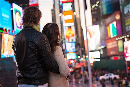 Young couple looking up at neon signs, New York City, USA Stock Photo - Premium Royalty-Free, Code: 614-07444088