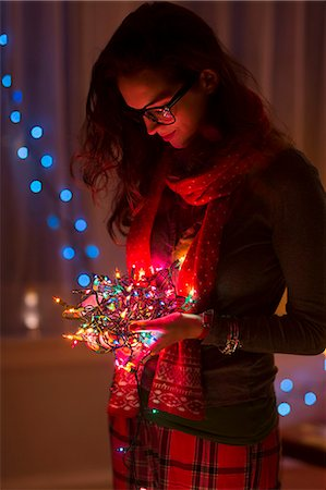 Young woman holding tangle of christmas lights Stock Photo - Premium Royalty-Free, Code: 614-07444159
