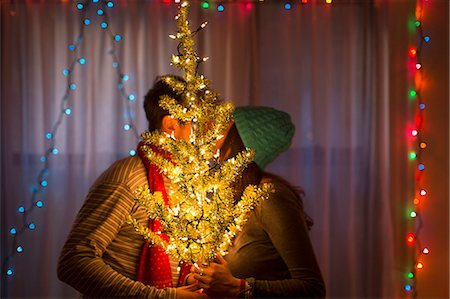 Young couple kissing behind illuminated christmas tree Stock Photo - Premium Royalty-Free, Code: 614-07444167