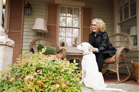 dog and woman and love - Senior woman sitting on porch rocking chair with dog Stock Photo - Premium Royalty-Free, Code: 614-07444198