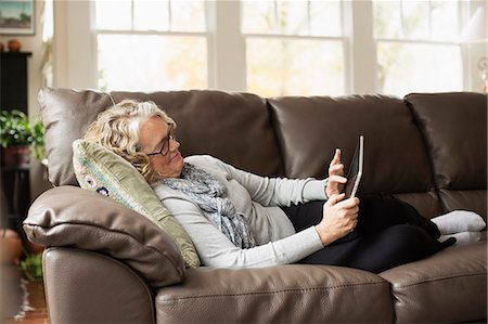 Senior woman relaxing on sofa with digital tablet Stock Photo - Premium Royalty-Free, Code: 614-07444211