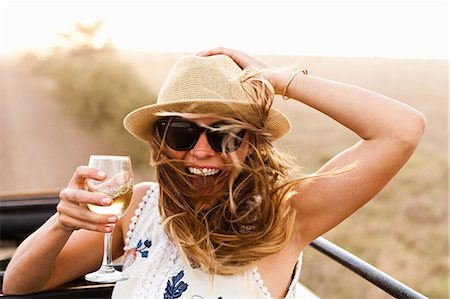 Young woman wearing hat holding glass of wine Stock Photo - Premium Royalty-Free, Code: 614-07444236