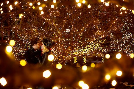 Young couple kissing surrounded by city xmas lights Stock Photo - Premium Royalty-Free, Code: 614-07444256