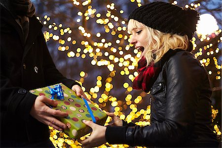 festive - Young woman receiving xmas gift on city street Stock Photo - Premium Royalty-Free, Code: 614-07444253