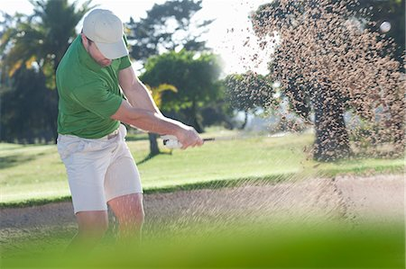 Young male golfer playing out of bunker Stock Photo - Premium Royalty-Free, Code: 614-07444267