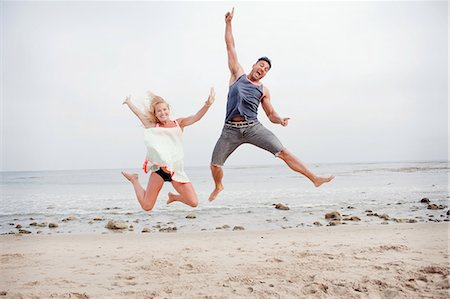 partnership - Pregnant couple jumping mid air on the beach Stock Photo - Premium Royalty-Free, Code: 614-07444315