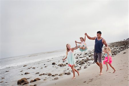 family active beach - Parents and two young girls walking on beach Stock Photo - Premium Royalty-Free, Code: 614-07444317