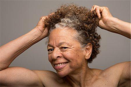 Close up studio portrait of senior woman pulling her hair Stock Photo - Premium Royalty-Free, Code: 614-07444329