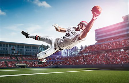 American football player catching ball mid air in stadium Stock Photo - Premium Royalty-Free, Code: 614-07444390